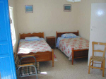 Marias main house twin bedroom with cot and large wardrobes at the other end of the room in Kalavassos Cyprus